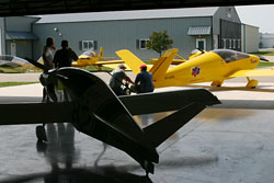 Fly-In attendees inspect the Y-tail of the Xenos Motorglider. Fly-In attendees were able to see the heritage of current Sonex Aircraft, as the Monex Racer, on loan from the EAA AirVenture Museum for refurbishment, was on display (foreground) along with the original prototype Sonerai I